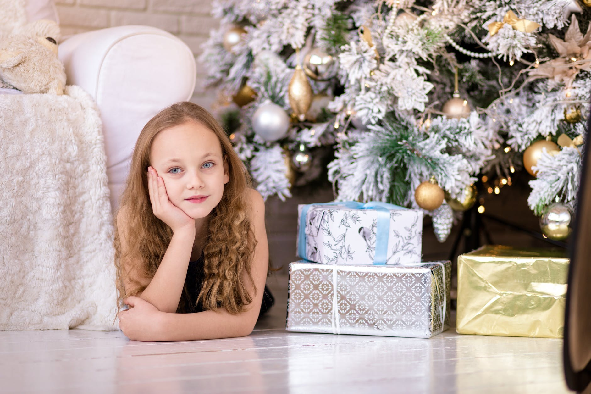 Little girl at the side of a beautiful silver and gold Christmas Tree