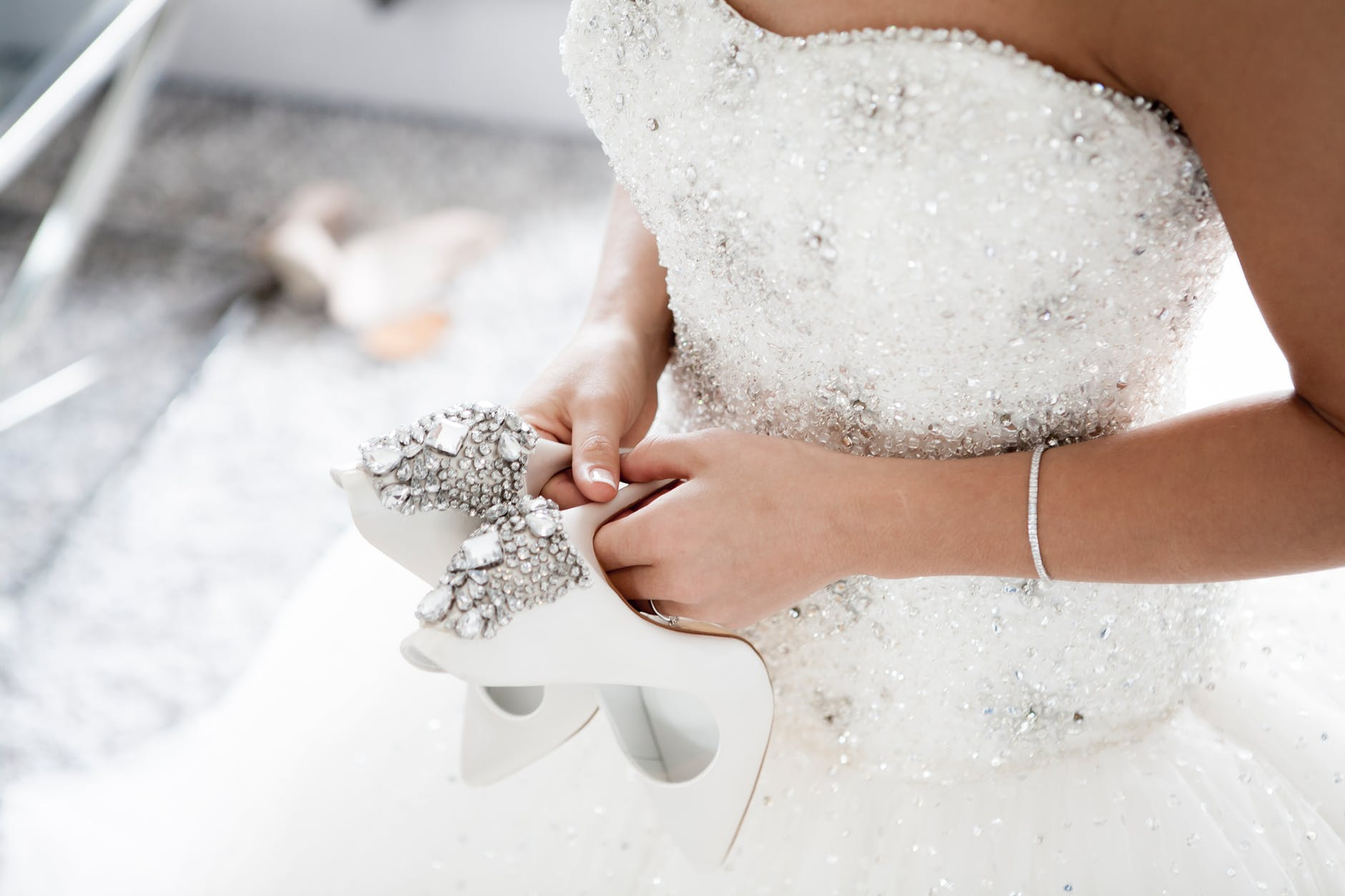 Bride in beautiful dress holding white high heels