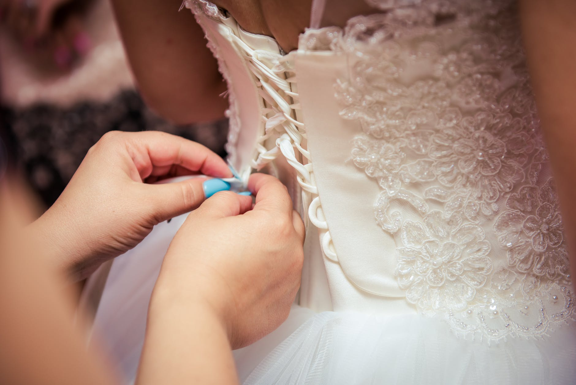Bride getting fastened into her dress