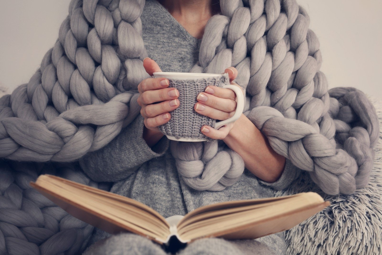 Woman wrapped in a chunky grey blanket