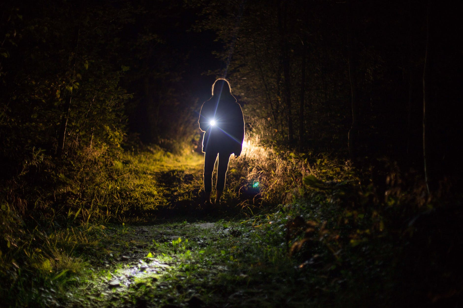 Person walking at night with flashlight