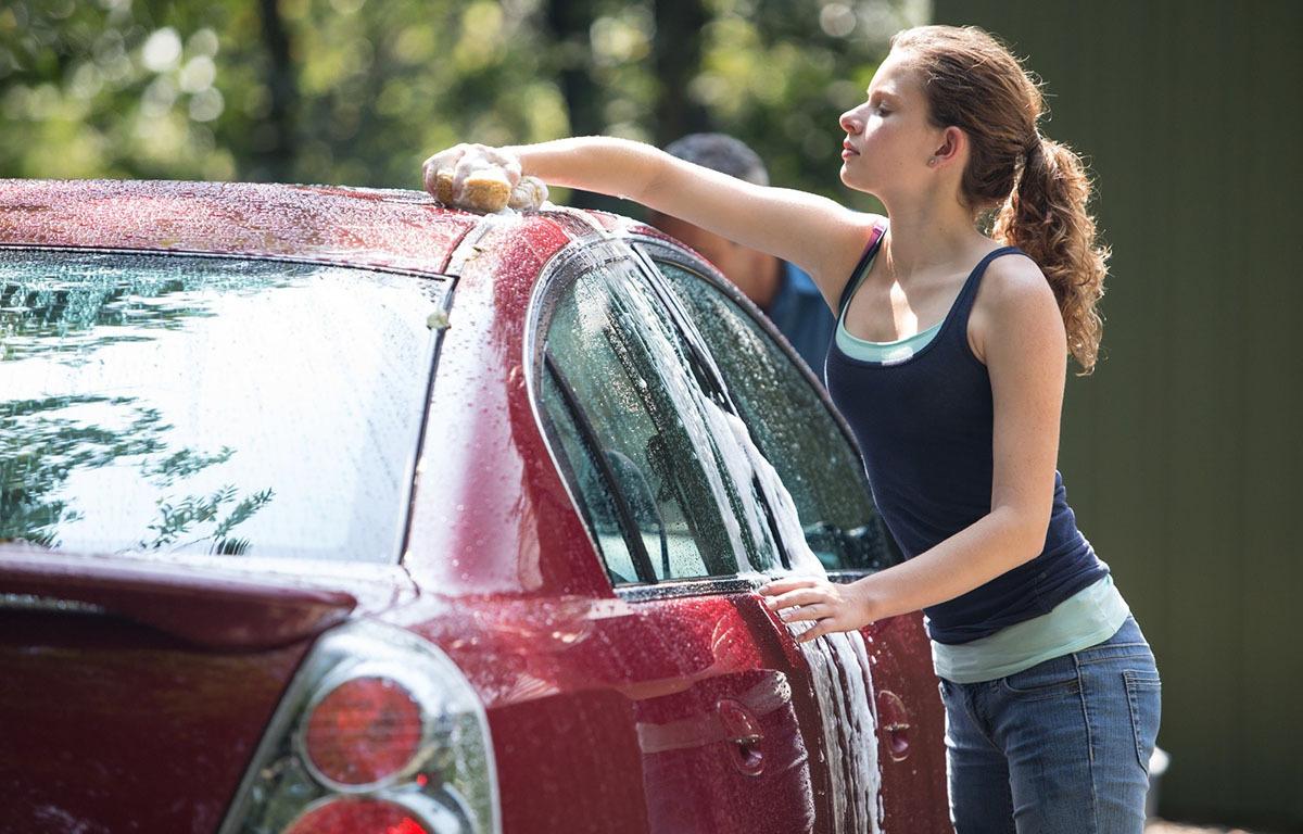 Woman washing a red car